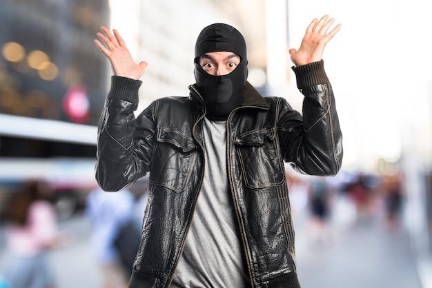 Разбойник делает неожиданный жест на несфокусированном фоне