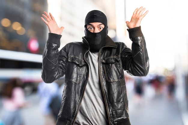 Robber doing surprise gesture on unfocused background