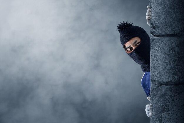 A robber hiding behind the wall | Photo: Freepik