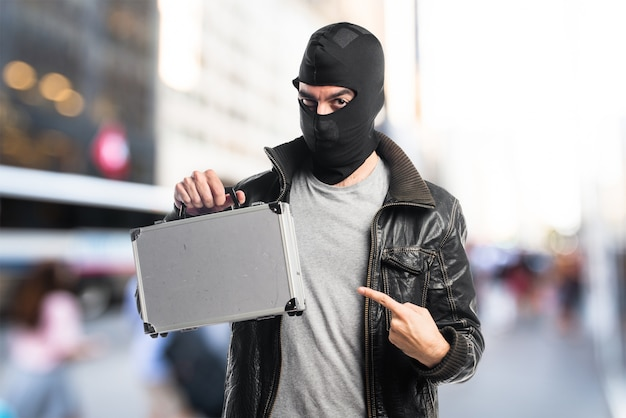 Robber holding a briefcase on unfocused background