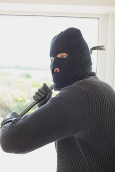 Robber holding a crowbar in his hands