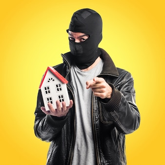 Robber holding a little house on colorful background