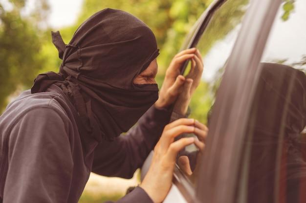 Грабитель стоит рядом с машиной и пытается украсть вещи