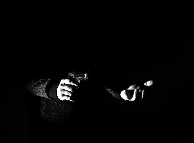 밤에 총을 든 강도. 위험한 범죄자. 돈을 습격하는 까마귀를 입은 남자. 경제 위기, 빈곤, 실업 개념. 격리에 대한 코로나바이러스 사람들 격리의 결과. 희망이 없다.