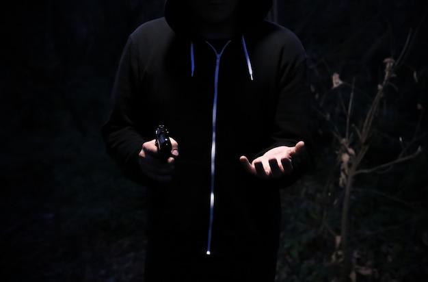 밤에 총을 든 강도. 위험한 범죄자. 돈을 훔치는 까마귀를 입은 남자. 프리미엄 사진