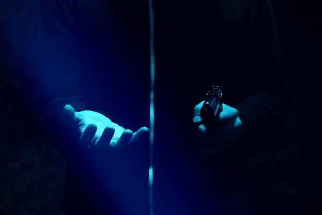 밤에 총을 든 강도. 위험한 범죄자. 돈을 훔치는 까마귀를 입은 남자.