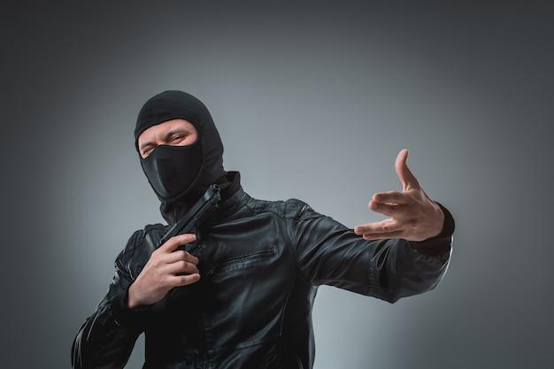 Robber with a gun, studio shot