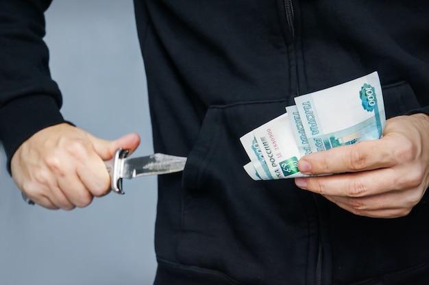 Грабитель с ножом в руке и российскими деньгами. бандит вытаскивает из кармана складной нож с угрозами. грабитель с ножом в толстовке с капюшоном. понятие преступления для слайда презентации. вымогательство денег.