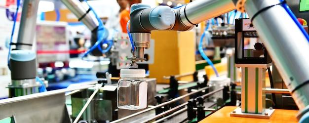 Рука робота установила стеклянную бутылку с водой на автоматическом промышленном оборудовании на заводе производственной линии