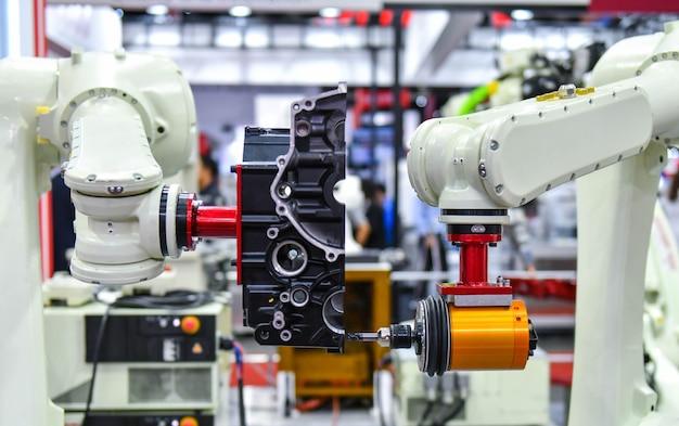 공장에서 엔진을 조립하기 위한 로봇 팔 기계 자동차 산업 개념