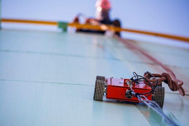 Робот-машина, поднимающаяся на толщину, пластина для хранения масла в резервуаре под рабочим-мужчиной, тянет за веревку