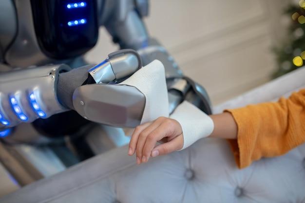 女の子の手首に包帯を慎重に取り付けるロボット