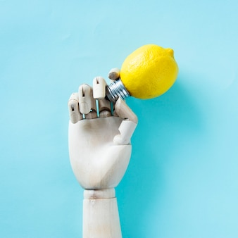 Рука робота держит лампочку лимона