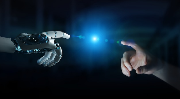 Robot hand making contact with human hand on dark background