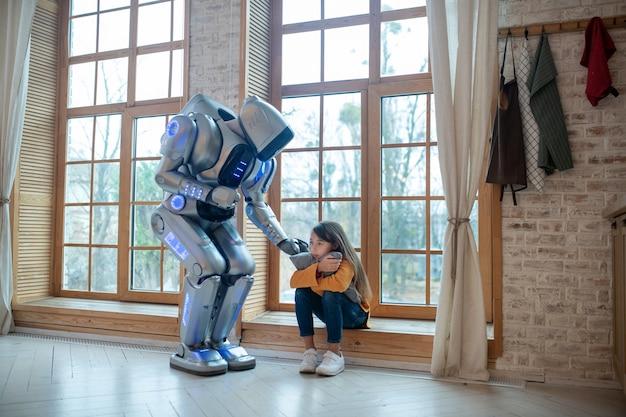 Робот разговаривает с девушкой, сидящей у окна