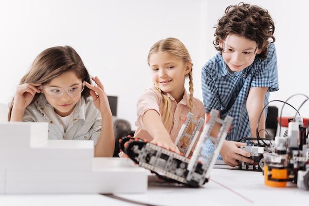 ロボットテスト。学校に座って、技術プロジェクトに取り組んでいる間サイバーロボットをテストしている気配りのある楽しいやる気のある子供たち