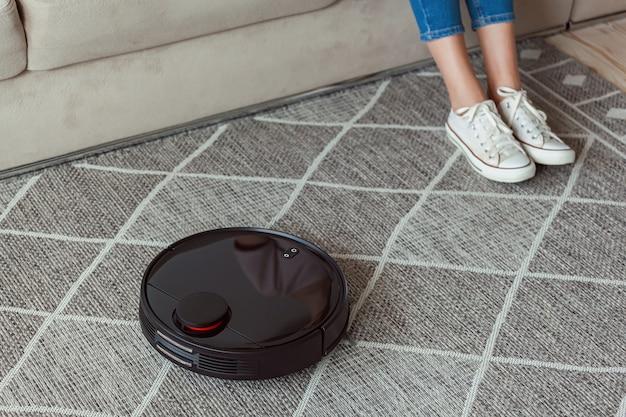 Робот-пылесос чистит ковер, ноги женщины отдыхают, сидя на диване у себя дома