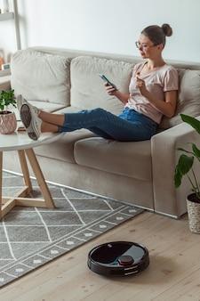 Робот-пылесос чистит ковер, женщина с дистанционным управлением мобильным телефоном и отдыхает, сидя на диване у себя дома