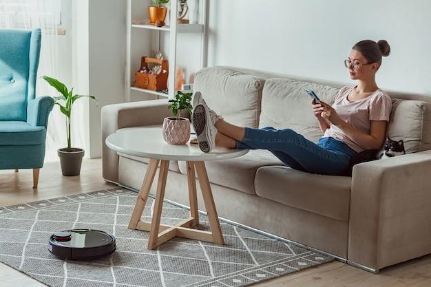 Робот-пылесос чистит ковер, женщина дистанционно управляет мобильным телефоном и наслаждается отдыхом, сидя на диване у себя дома