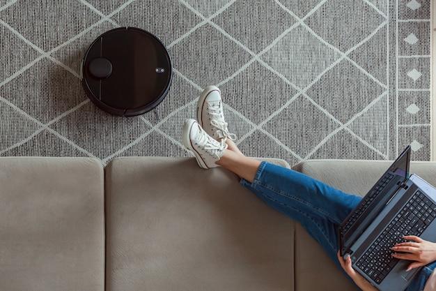 Робот-пылесос чистит ковер, женщина с ноутбуком сидит на диване у себя дома