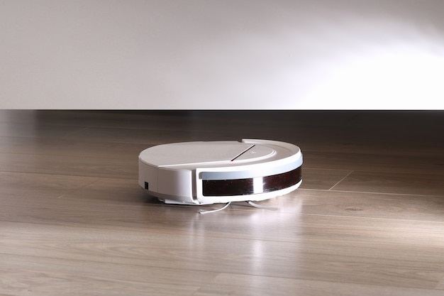 The robot vacuum cleaner cleans under the bed.