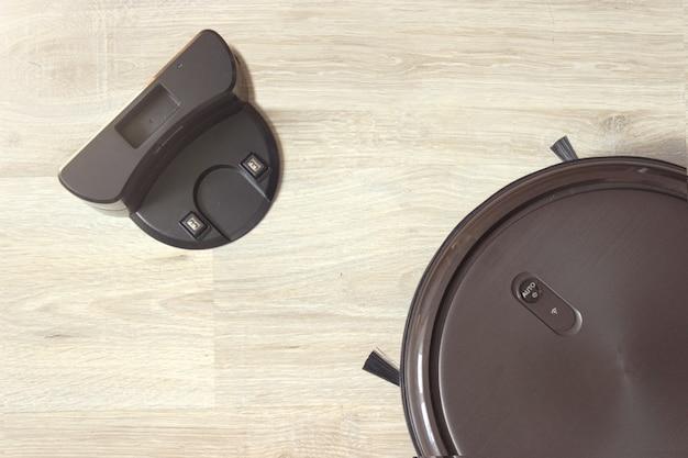 Робот-пылесос на зарядной станции после его завершения. современное умное электронное ведение домашнего хозяйства