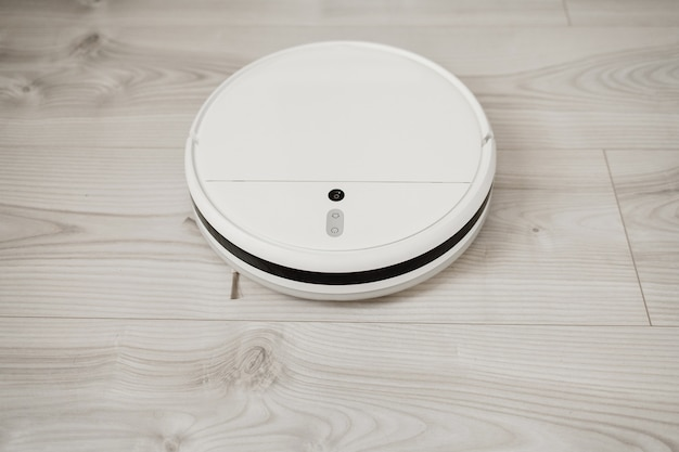 Robot vacuum cleaner performs automatic cleaning laminate of the apartment. smart home.