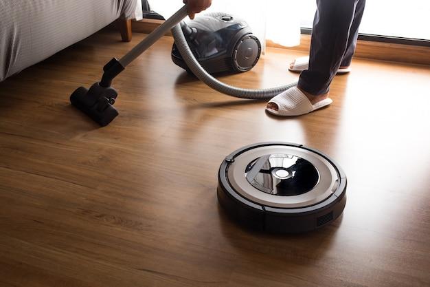 사람들과 함께하는 로봇 청소기는 바닥을 청소합니다.