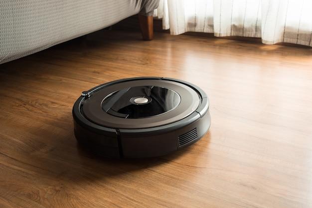Robot vacuum cleaner on wood,laminate floor.smart life concepts ideas