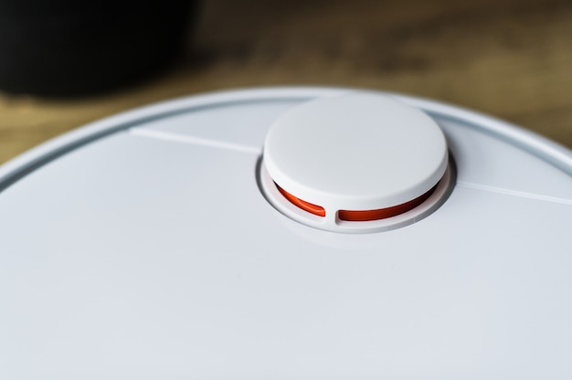 Robot vacuum cleaner on wooden floor. side view. smart home concept. automatic cleaning.