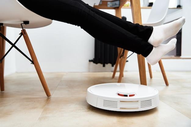 여자가 휴식하는 동안 가구와 함께 바닥에 작업하는 로봇 진공 청소기. 현대적인 스마트 가구