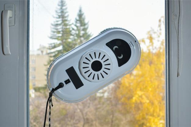 秋の風景と窓の背景にある窓やセラミックタイルを掃除するためのロボット洗濯機