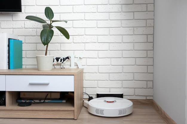 Робот-пылесос на зарядной станции в современной гостиной. автоматический помощник для уборки дома concept
