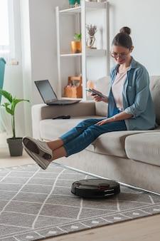 ロボット掃除機のクリーニングカーペット、女性のリモコンの携帯電話と自宅のソファに座って休息をお楽しみください