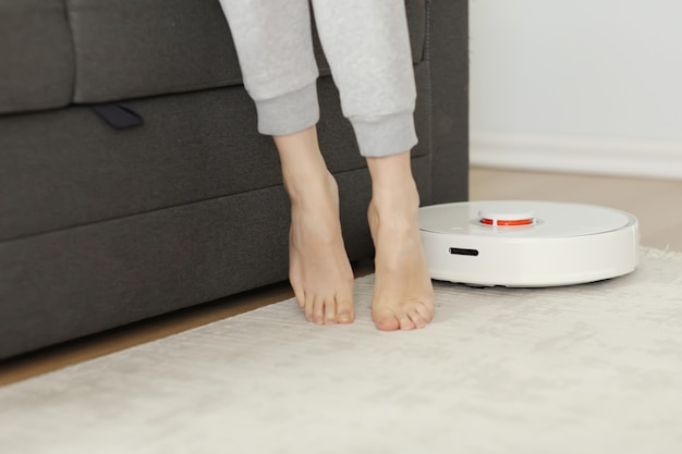 Robotic vacuum cleaner cleaning the room while woman resting on sofa. selective focus on robotic