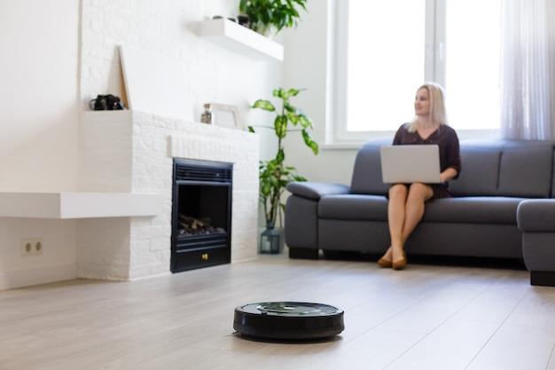 여자가 소파에 쉬고 있는 동안 방을 청소하는 로봇 청소기