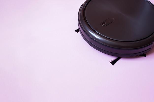 ロボット掃除機。ピンクの背景に自律型ロボットのクローズアップ。