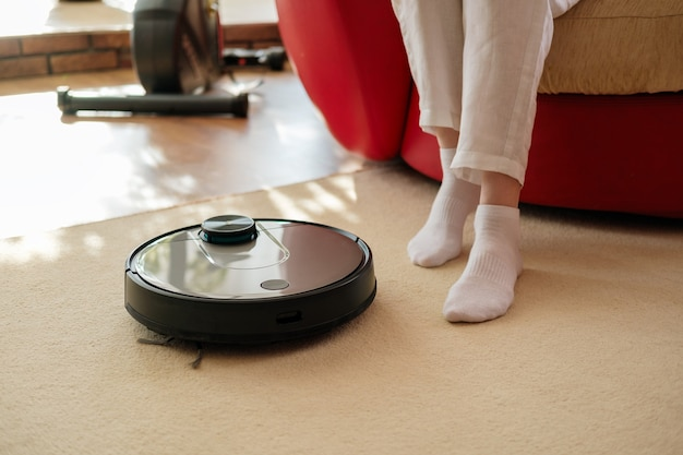 Robotic vacuum cleaner and legs on carpet, lazy and comfortable home, slow living concept, rest