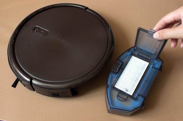 바닥에 있는 로봇 청소기, 스마트 청소 기술, 먼지통 청소.