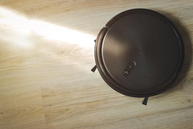 작동 중인 라미네이트 바닥의 로봇 청소기. 가사와 기술 개념입니다.