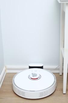 Робот-пылесос на ламинатном деревянном полу заряжается от базовой станции. умная технология очистки. робот-пылесос возвращается к зарядке в доке на полу чистой комнаты.