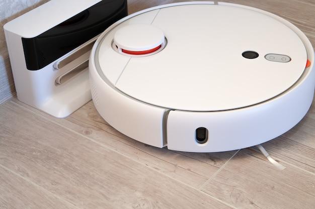 Робот-пылесос на ламинатном деревянном полу заряжается от базовой станции. умная технология очистки.