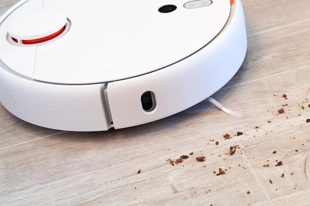로봇 청소기는 라미네이트 나무 바닥에서 빵 부스러기를 제거합니다. 스마트 청소 기술.