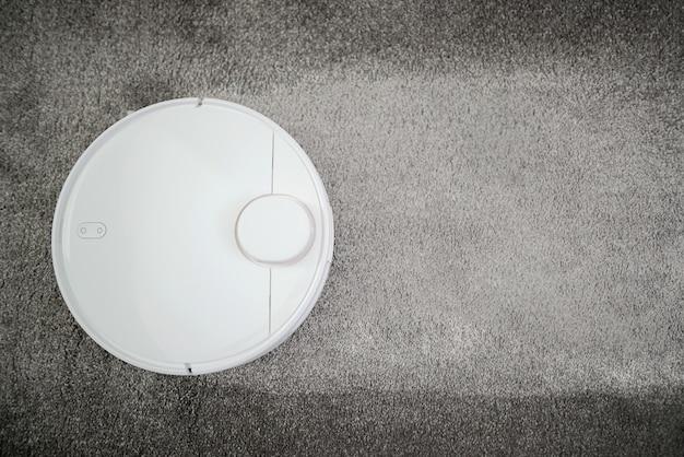 로봇 진공 청소기 작동. 자동화 청소. 흰색 로봇 청소기는 카펫에 먼지, 머리카락을 수집합니다. 로봇 청소기 청소 바닥. 평면도. 로봇 진공.