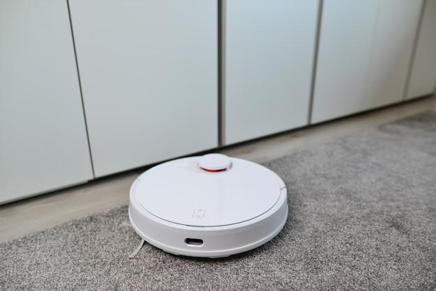 カーペットに取り組んでいるロボット掃除機。自動洗浄。白いロボット掃除機がほこりを集めます。現代のスマートデバイスの床の掃除。