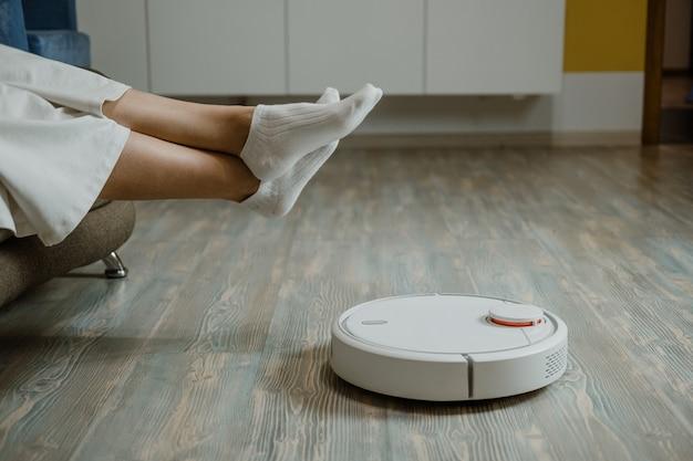 로봇 청소기 로봇은 스마트 홈 로봇 청소기를 걸레질하고 여성은 자동 소파에서 휴식을 취합니다.