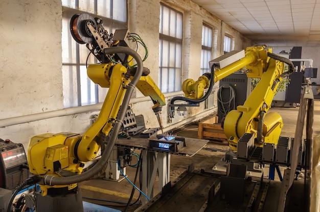 生産中のロボット。工場フロアでの溶接ロボットとマニピュレーターロボットの作業