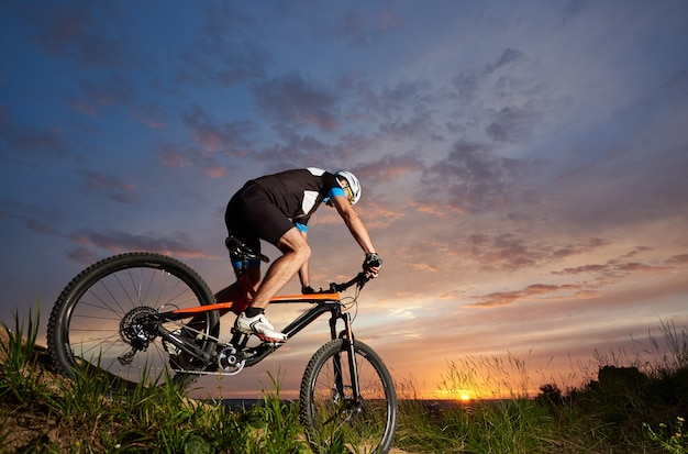 Robust and sporty man sitting on bicycle and cycling. energetic cyclist riding bike on trail with grass