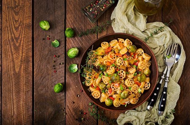 Вегетарианская овощная паста rocchetti с брюссельской капустой, помидорами, баклажанами и паприкой в коричневой миске на деревянном столе. вид сверху