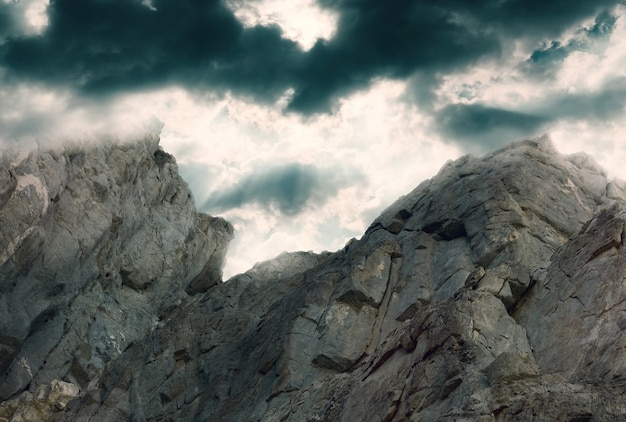 Rock against a dark dramatic sky with clouds